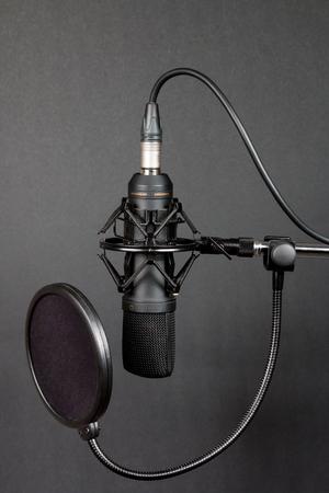 condenser: Black condenser microphone with pop filter on grey background