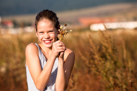 11 years: Beautiful, 11 years old girl in the field, smiling and holding some flowers Stock Photo