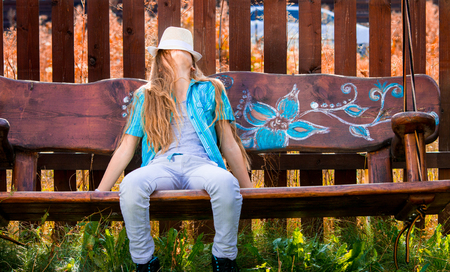 11 years old: Blonde, 11 years old girl in blue shirt sitting on a garden swing, covering her face with a white hat. Autumn colors