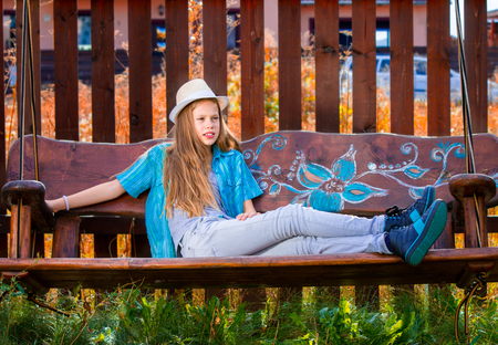 11 years: Beautiful 11 years old girl sitting on a garden swing, wearing a white hat. Autumn colors.