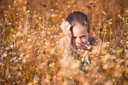 11 years: Beautiful, 11 years old girl in the field sitting between flowers