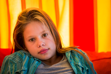 11 year old girl: Head shot of a beautiful, 11 years old girl sitting in front of a red and orange curtain