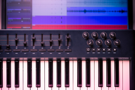 daw: Midi keyboard and controller with faders and buttons. Waveforms in a DAW are visible in the background