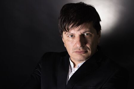 40 year old man: Handsome man in his 40s looking in the camera with a serious attitude. Wearing white shirt and a black jacket. Stock Photo
