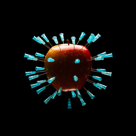hypodermic needles: A red apple full of hypodermic needles, isolated on black background. Stock Photo