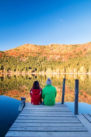 ragazza innamorata: Coppia giovane seduto su un molo, sulla riva di un lago. L'acqua sta riflettendo foresta di autunno. La Luna è visibile nel cielo.
