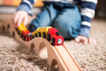 Detail of a little boy playing with wooden train indoors. Narrow depth of field