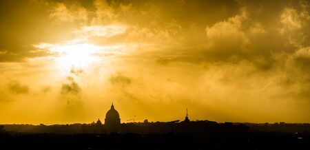 Golden sunset with clouds over the city of Rome, Italy. The silhouette of St. Peters Basilica (Basilica Papale di San Pietro in Vaticano) is seen on the horizon. Stock Photo