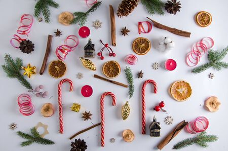 Chaotic Christmas and New Year decorations lie on a white background: fir branches, lollipops, candles, dried orange, dried apples, cinnamon sticks, anise stars, cones, wooden stars, Christmas toys, cotton, tinsel. Colorful picture for the New Year mood.