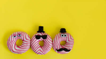 Funny donuts with funny eyes, hats and mustaches on yellow background, creative sweets concept with copy space