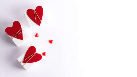 The concept of the background to Valentines Day. Three white boxes with hearts lie on a white background. Copying space