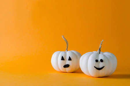 Funny white pumpkins on an orange background, minimalism of the festive background Happy Helloween, copying text Imagens