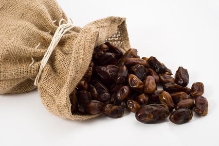 Burlap sack with palm dates spilling out over a white background Stock Photo - 5793402