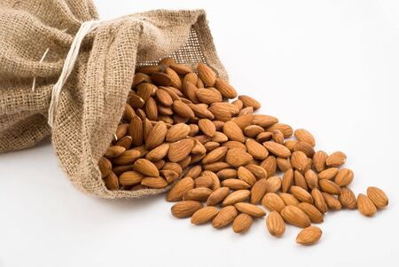 Burlap sack with almonds spilling out over a white background Stock Photo