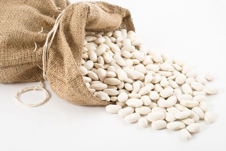 Burlap sack with white beans spilling out over a white background Stock Photo