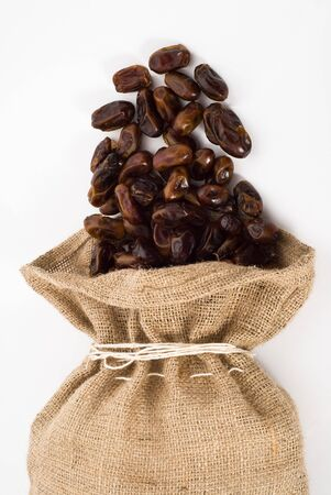 Burlap sack with palm dates spilling out over a white background  Stock Photo - 5851312
