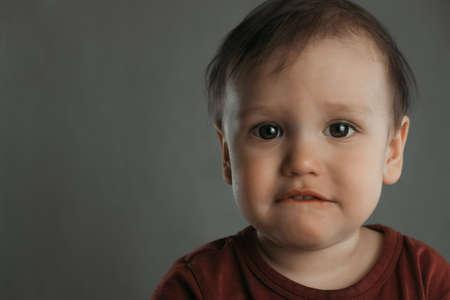 Portrait of a scared little boy with a bitten lip, on a gray background Фото со стока