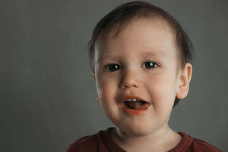 Portrait of a cute little boy showing tongue, on gray background Banque d'images