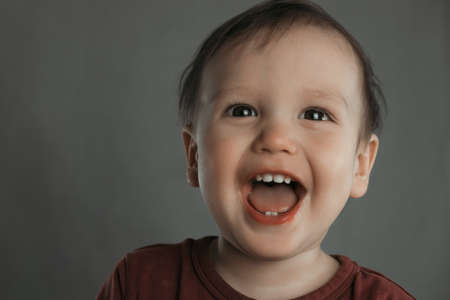 Portrait of a cute laughing little boy on a gray background Banque d'images