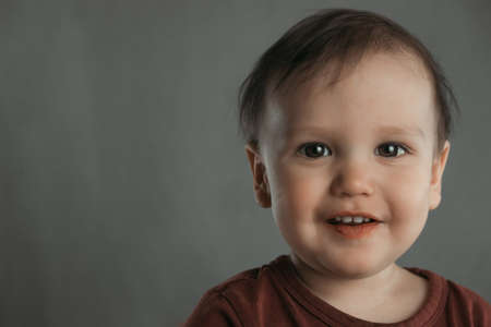 Portrait of a cute smiling little boy on a gray background