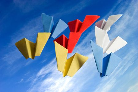 darts flying: abstract origame paper planes folded from colored sticknotes on cloudy sky background