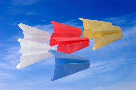 Origami paper planes on clouds sky background photo