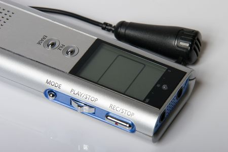 dictating: digital sound recorder and microphone for interview on real reflecting white plastic background
