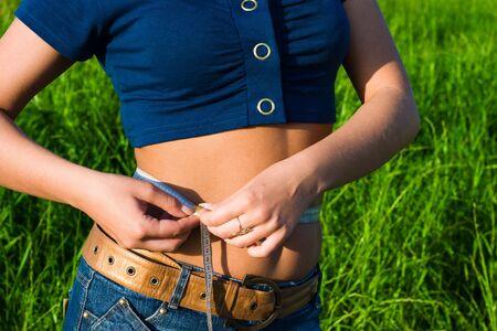 허리의 잘룩 한 선: Young woman measuring waistline 스톡 사진