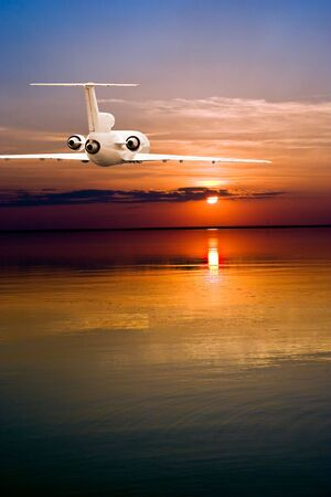Commercial airliner fluing over water to sun photo