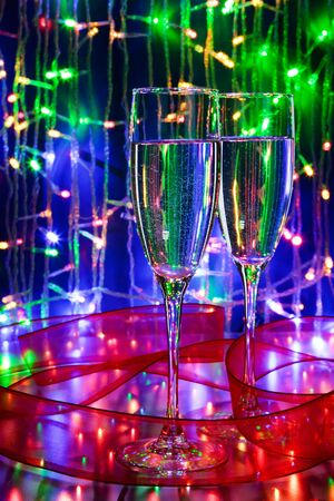 romantics: Two glasses of champagne with christmas lights on blue background Stock Photo