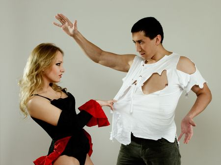 Handsome man and pretty woman dancing over gray background photo
