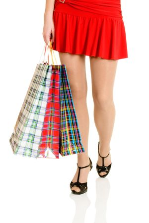 Sexy female legs with shopping bags isolated over white background photo
