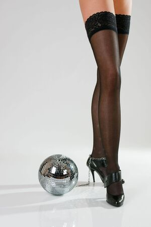 Long sexy female legs and disco ball photo