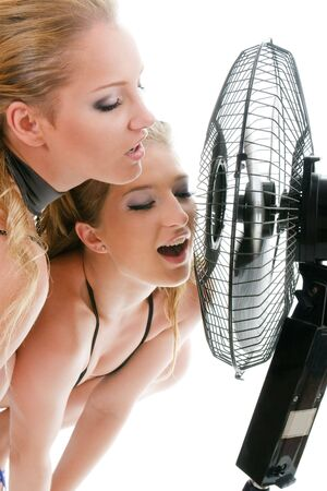 Two blonde woman under fan breeze isolated over white background photo