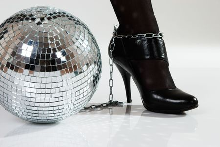 ball and chain: mirrored disco ball as fetters enchained to leg