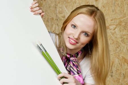 Young woman showing white board and holding paint brushes Stock Photo - 6326595