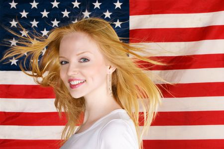 Portrait of happy beautiful teen girl against american flag photo