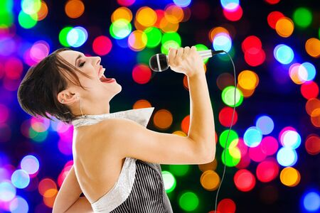 Singer artist performance at a night club against colored lights wall photo