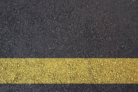 Dark asphalt surface photo with yellow line