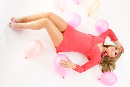 Portrait of beautiful young woman in mini dress lying down on floor isolated over white background photo