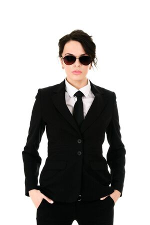 spy glass: Serious businesswoman in black glasses holding hands in pockets isolated on white background