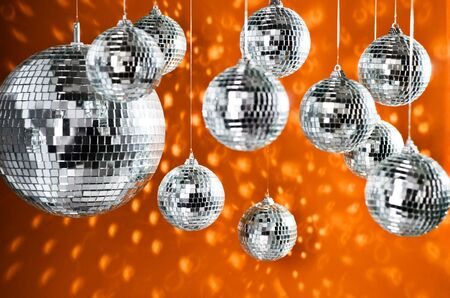 mirrored: Mirrored disco balls with light spots over orange background Stock Photo