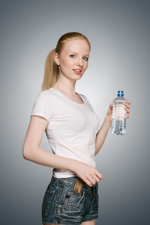 standing water: Young blonde girl with plastic bottle of water Stock Photo