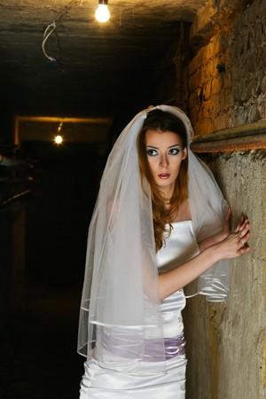 Frightened bride in white wedding dress   inside dungeon Stock Photo - 7907803