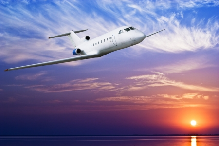 Airliner flying above tropical sea at sunset Stock Photo - 8043462