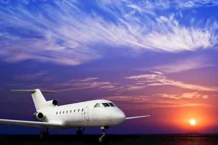 transporte terrestre: Avi�n jet sobre terreno y espectacular puesta de sol  Foto de archivo
