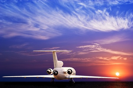 private jet: Passenger jet airliner on ground and stunning sunset