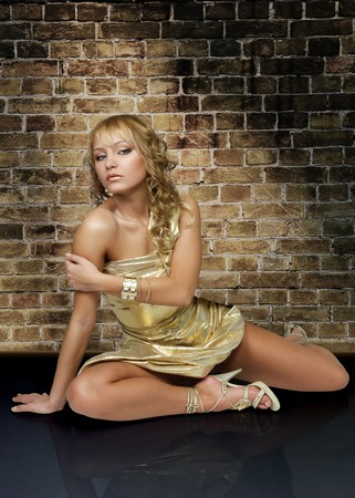 glamur: Sexy young woman in golden dress against a brick wall