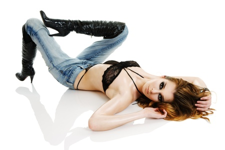 Seductive young woman wearied in black lingerie lying down on floor isolated over white background photo