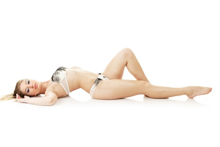 is slender: Beautiful slim sexy woman lying down isolated over white background